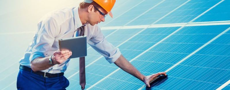 Engineer at solar power station with solar panel tablet checks.
