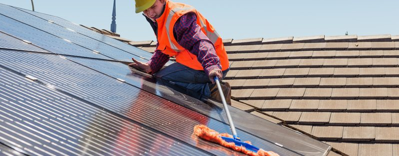 Young worker cleaning solar panels on the roof.Focus on the worker.